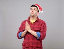 Young man in Santa hat praying Royalty Free Stock Photos