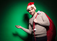 Young man in santa hat  is presenting Stock Photo