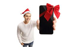 Young man with a santa hat showing a phone wrapped with red ribb Stock Images