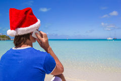Young man in santa hat talking on phone at Stock Image