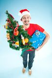 A young man in a Santa hat wiht Christmas gift Royalty Free Stock Photography