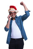 Young man in santa hat is winning on phone Stock Photos