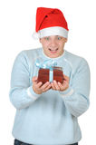 Young man in santa's hat holding present box Stock Images
