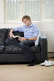Young man sat on a sofa reading a book Stock Photos