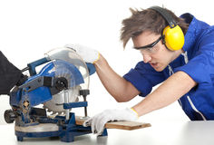 Young man with saw preparing for cutting Royalty Free Stock Images