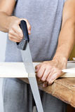 Young man sawing a wooden board with a handsaw Royalty Free Stock Image
