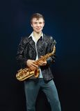 Young man with saxophone Stock Images