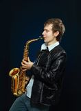 Young man with saxophone. Studio portrait of young hip cool man with saxophone on dark background Stock Image