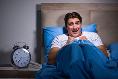 The young man scared in bed. Young man scared in bed Royalty Free Stock Photo
