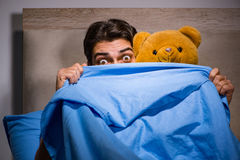 The young man scared in bed. Young man scared in bed Royalty Free Stock Image