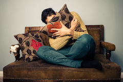 Young man is scared and hiding his face behind a cushion. Young man sitting on an old vintage sofa is scared of something and hiding his face behind a cushion Stock Image