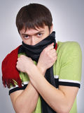 Young man in a scarf heats hands Stock Photos