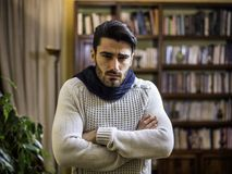 Young man with scarf, holding his arms crosssed for coldness. At home in his living room stock image