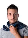 Young man with scarf, holding his neck because of throat ache Stock Photography