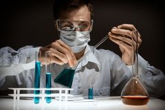 Young man scientist using auto-pipette with flask in medical science laboratory. Researcher concept. royalty free stock photos