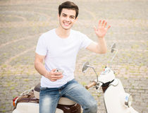 Young man on scooter. Front view of handsome man with phone sitting on scooter and posing to camera Stock Photo