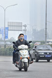 Young man on a scooter with mouth cap, beijing, China Stock Image