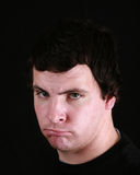 Young man scowling Royalty Free Stock Images
