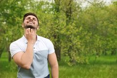 Young man scratching neck outdoors. Seasonal allergy. Young man scratching neck outdoors, space for text. Seasonal allergy stock photos