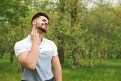 Young man scratching neck outdoors. Seasonal allergy. Young man scratching neck outdoors, space for text. Seasonal allergy stock image