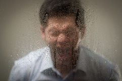 Young man is screaming, behind a blurred window with drops, gray background.  Royalty Free Stock Photography