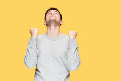 The young man screaming with delight. On yellow studio background stock photo