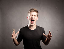 Young man screaming. On a grey background Royalty Free Stock Image