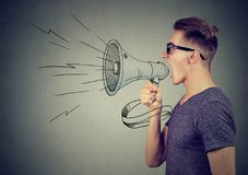 Man screaming in a megaphone making announcement. Young man screaming in a megaphone making announcement royalty free stock images