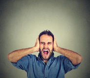Young man screaming mouth open, holding head with hands Royalty Free Stock Images