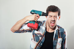 Young man screaming. Portrait of young man screaming holding drill near his head posing next to color background Stock Image