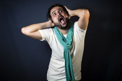 Young man screaming and pulling their hair. On black background Stock Photo
