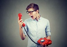 Young man screaming on the phone. Young man screaming on the red telephone Royalty Free Stock Photography