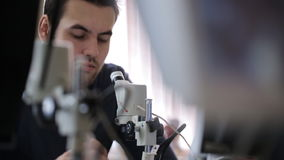 Young man screws up his eyes to look object into microscope. stock video footage
