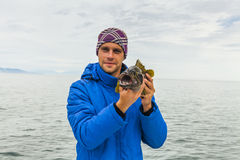 Young man with sea bass. Royalty Free Stock Image