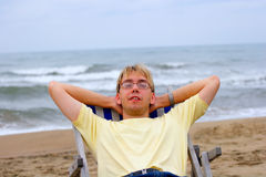 Young man on sea beach. In longue Stock Image