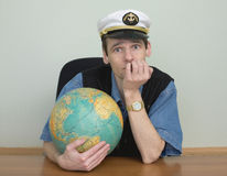 Young man in a sea cap of captain with globe Royalty Free Stock Photography