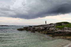 Young man by the sea. Man raising his hands up staying on the rock on the cloudy sky and sea background Stock Photos