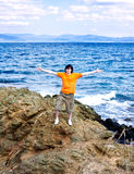 The young man at the sea on a stone Royalty Free Stock Photos