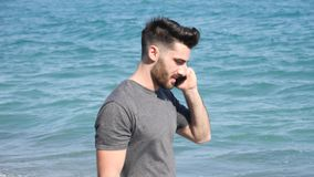 Young man by the sea talking on mobile phone. Athletic man at the seaside using cell phone to call someone with the sea behind him stock video