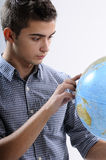 Young man searching. On globe destinations for his vacations, studies Royalty Free Stock Image