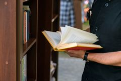 Young man searching for a book in bookstore. university student. Selecting a book in bookshelf library. male college student, education research and self Royalty Free Stock Photography