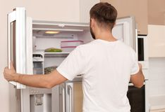 Young man searching for food in refrigerator. At home stock photography