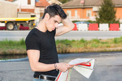 Young man searching for a location from printed Stock Image