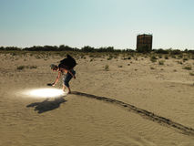 Young man searching through sand with light. Young man with backpack searching through the sand, with a bright light stock images