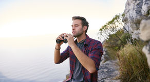 Young man searching for sights with his binoculars outdoors Stock Photos