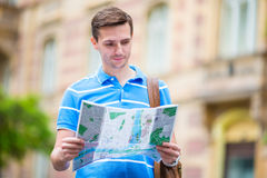 Young man searching the street with a city map in Europe. Caucasian tourist looking at the map of European city in Stock Images