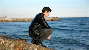 Young man at the seaside along the shore overlooking the ocean or sea stock video