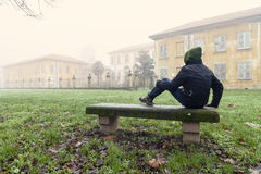 Young man seated on a bench. A young man alone seated on a bench looking an ancient palace royalty free stock images
