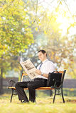 Young man seated on a bench reading a newspaper in a park Stock Images