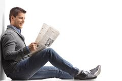 Young man seated on the floor reading a newspaper and leaning ag Stock Image